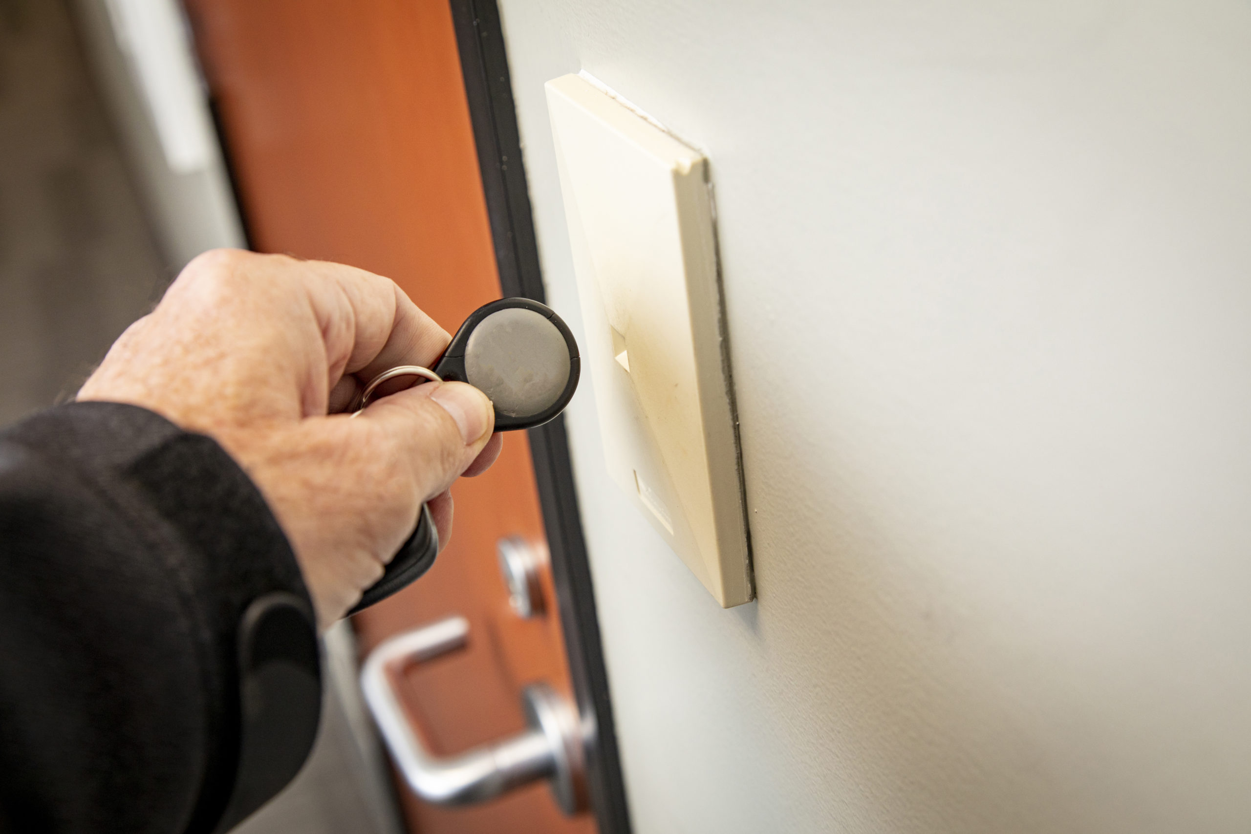 Security key fob in use, opening a door.