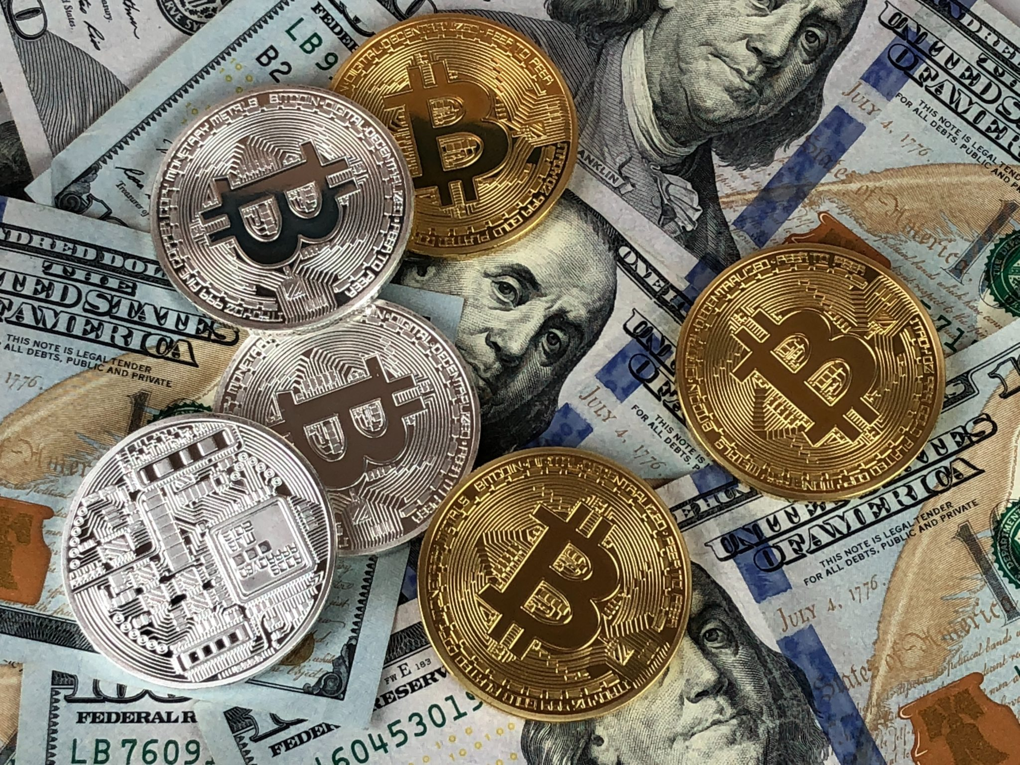 A picture of paper currency lying behind a handful of gold and silver coins with cryptocurrency symbols like Bitcoin. Cryptocurrency is a growing method for storing digital assets, consumer purchases, and long-term investment.